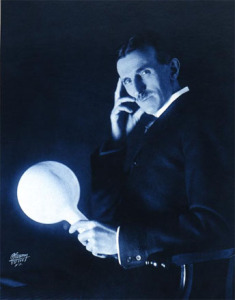 "Nikola Tesla holding a light bulb, illuminated without wires by an electromagnetic field from the ""Tesla Coil"""