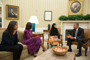 United States President Barack Obama (right), First Lady Michelle Obama (second from left), and their daughter Malia (left) meet with Malala Yousafzai (second from right), a young Pakistani schoolgirl who was shot in the head by the Taliban in 2012, in the Oval Office on 11 October 2013. Image Credit: White House/WikiMedia