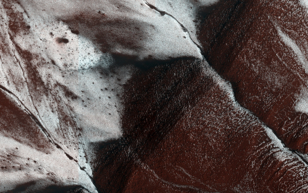 This newly released NASA image shows an area on the surface of Mars (approximately 1.5 by 3 kilometers in size) with frosted gullies on a south-facing slope within a crater. Image credit: NASA