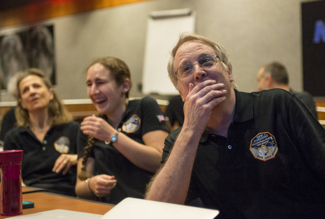 Members of the New Horizons science team react to seeing sharpest image of Pluto before closest approach. Photo Credit: (NASA/Bill Ingalls)