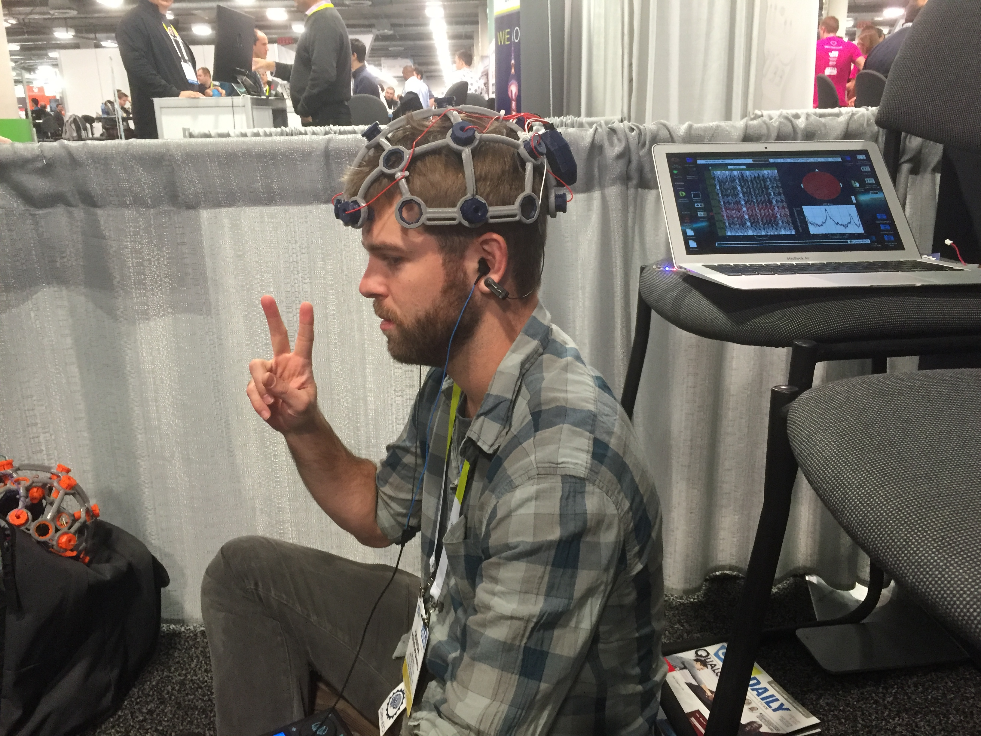 Conor wears Open BCI's Ultracortex next to a monitor that's showing his EEG.