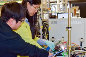 Graduate student Xiaofei Ye (left) helps postdoctoral scholar Liming Zhang adjust an experimental device that, confounding conventional wisdom, showed that heating metal oxide solar cells increased their efficiency. Credit Tom Abate