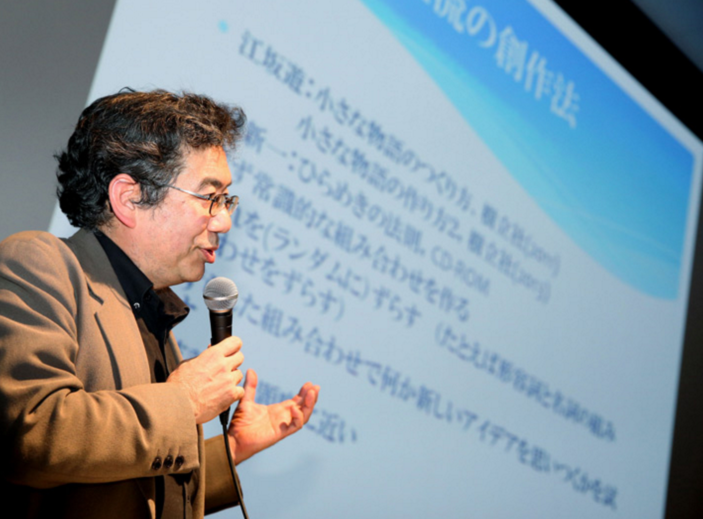 Hitoshi Matsubara, a professor of artificial intelligence at Future University Hakodate, talks about his team's AI project in Tokyo's Minato Ward on March 21. (Naoko Kawamura)