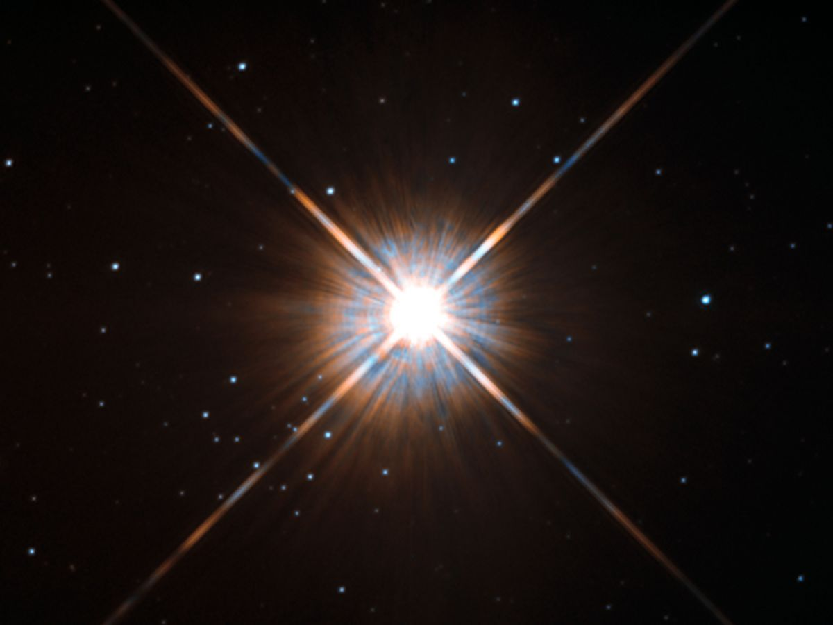 """Shining brightly in this Hubble image is our closest stellar neighbour: Proxima Centauri. Proxima Centauri lies in the constellation of Centaurus (The Centaur), just over four light-years from Earth. Although it looks bright through the eye of Hubble, as you might expect from the nearest star to the Solar System, Proxima Centauri is not visible to the naked eye. Its average luminosity is very low, and it is quite small compared to other stars, at only about an eighth of the mass of the Sun. However, on occasion, its brightness increases. Proxima is what is known as a """"flare star"""", meaning that convection processes within the star's body make it prone to random and dramatic changes in brightness. The convection processes not only trigger brilliant bursts of starlight but, combined with other factors, mean that Proxima Centauri is in for a very long life. Astronomers predict that this star will remain middle-aged — or a """"main sequence"""" star in astronomical terms —for another four trillion years, some 300 times the age of the current Universe. These observations were taken using Hubble's Wide Field and Planetary Camera 2 (WFPC2). Proxima Centauri is actually part of a triple star system — its two companions, Alpha Centauri A and B, lie out of frame. Although by cosmic standards it is a close neighbour, Proxima Centauri remains a point-like object even using Hubble's eagle-eyed vision, hinting at the vast scale of the Universe around us."""