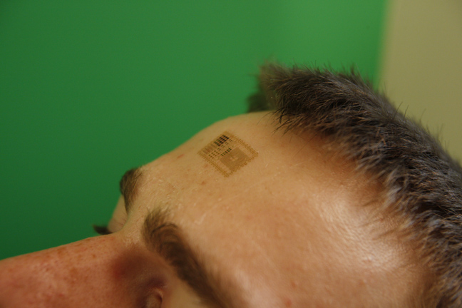 Electronic patch applied to the forehead to measure brain activity. Photo courtesy: John Rogers