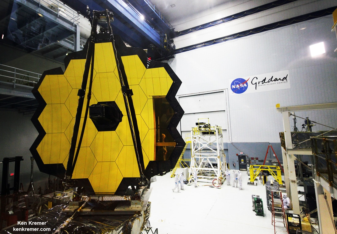 Technicians work on the James Webb Space Telescope in the massive clean room at NASA's Goddard Space Flight Center, Greenbelt, Maryland, on Nov. 2, 2016, as the completed golden primary mirror and observatory structure stands gloriously vertical on a work stand, reflecting incoming light from the area and observation deck. Credit: Ken Kremer/kenkremer.com