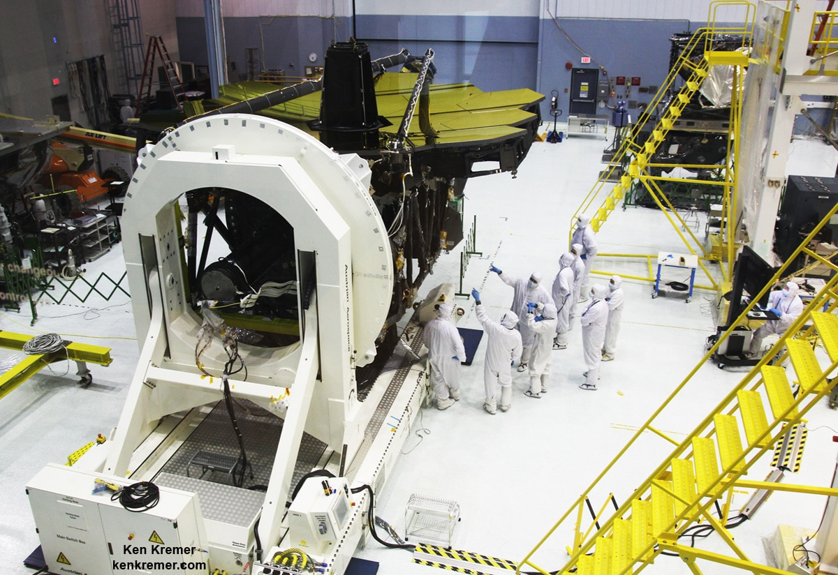 All 18 gold coated primary mirrors of NASA's James Webb Space Telescope are seen fully unveiled after removal of protective covers installed onto the backplane structure, as technicians work inside the massive clean room at NASA's Goddard Space Flight Center in Greenbelt, Maryland on May 3, 2016. The secondary mirror mount booms are folded down into stowed for launch configuration. Credit: Ken Kremer/kenkremer.com
