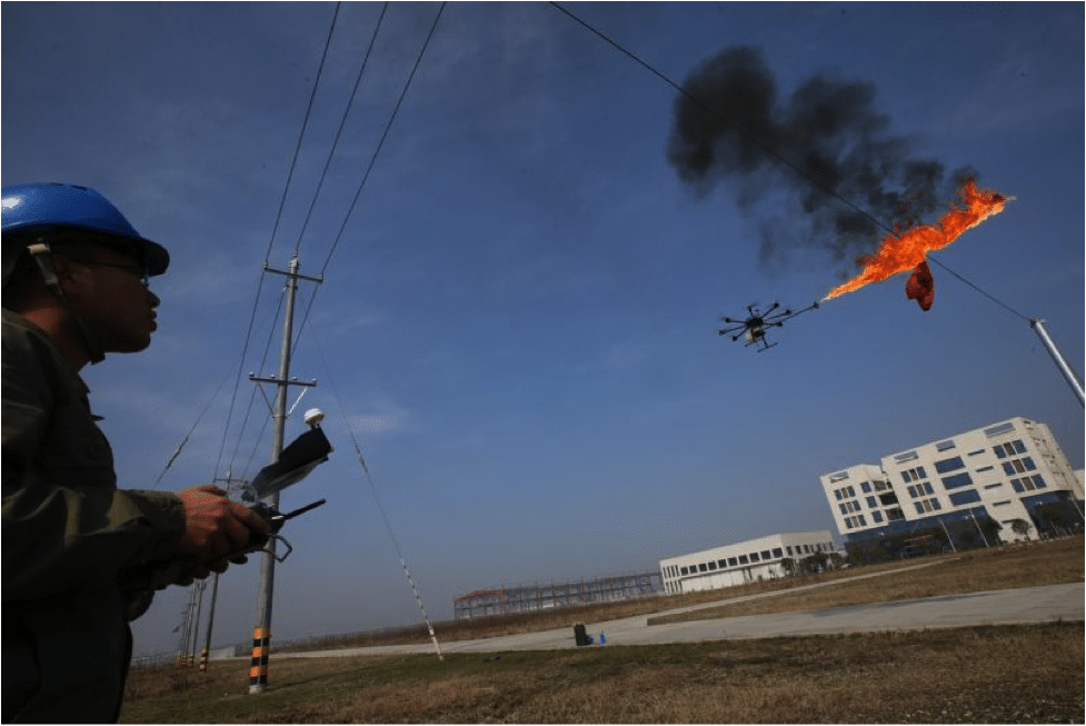 Electric company maintenance workers utilizing the drone flamethrower to clean electrical wires that have garbage attached to them. Photo by Wang Hu/VCG