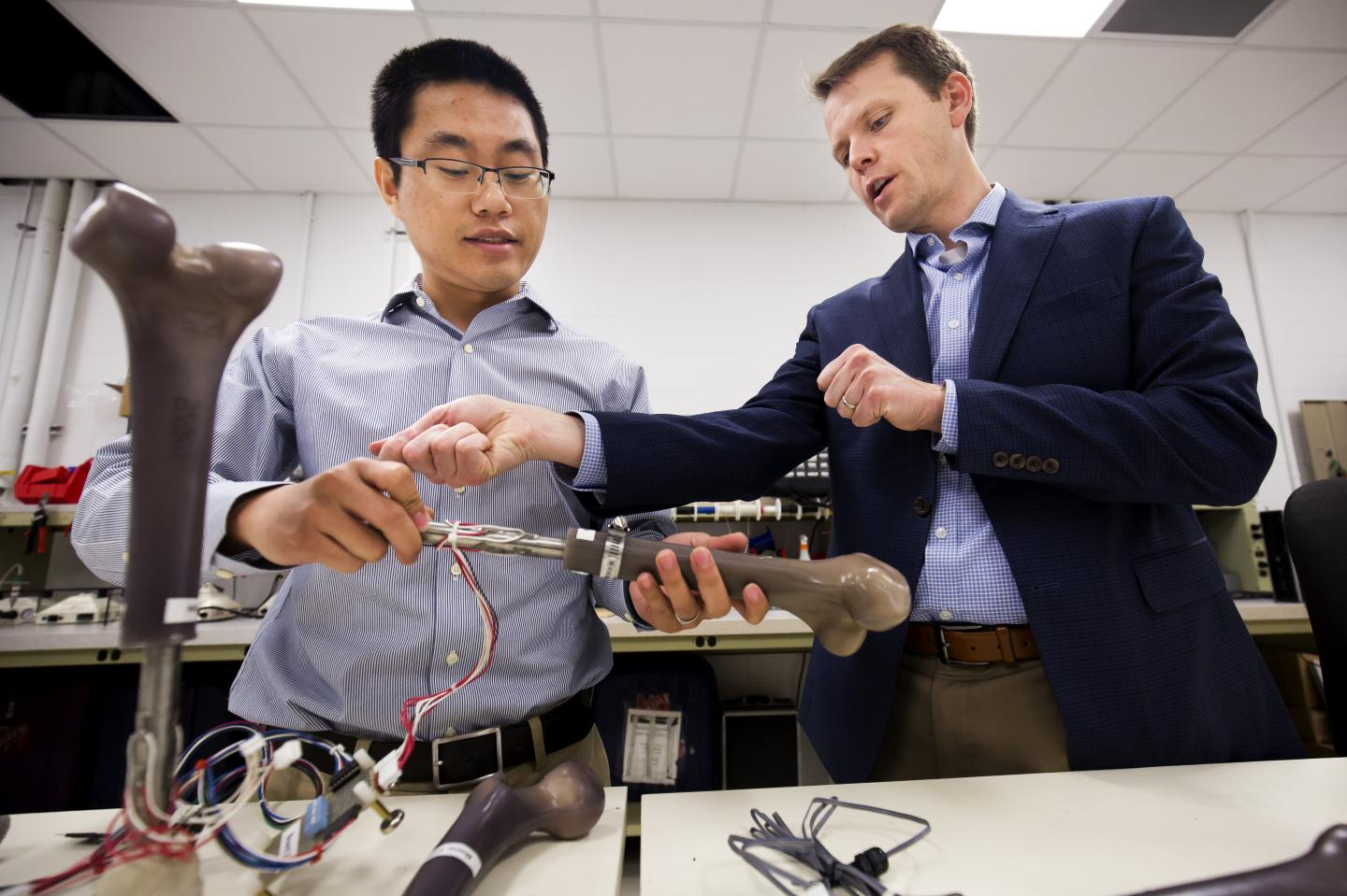 University of Michigan's Dr. Jerome Lynch examines a prototype of their smart artificial limbs with research fellow Wentao Wang.