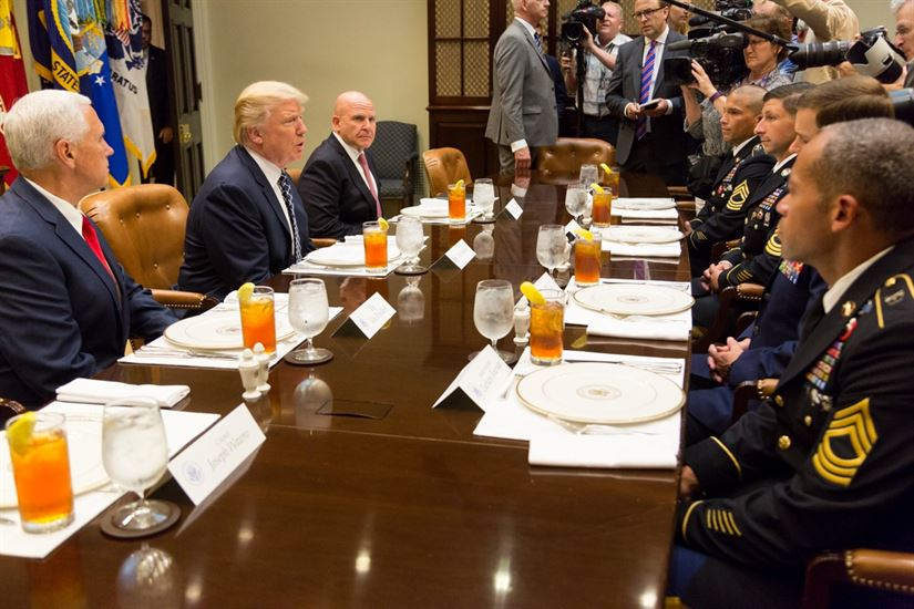 US President Donald Trump sits at a table with military advisors, perhaps discussing the climate change national security strategy.