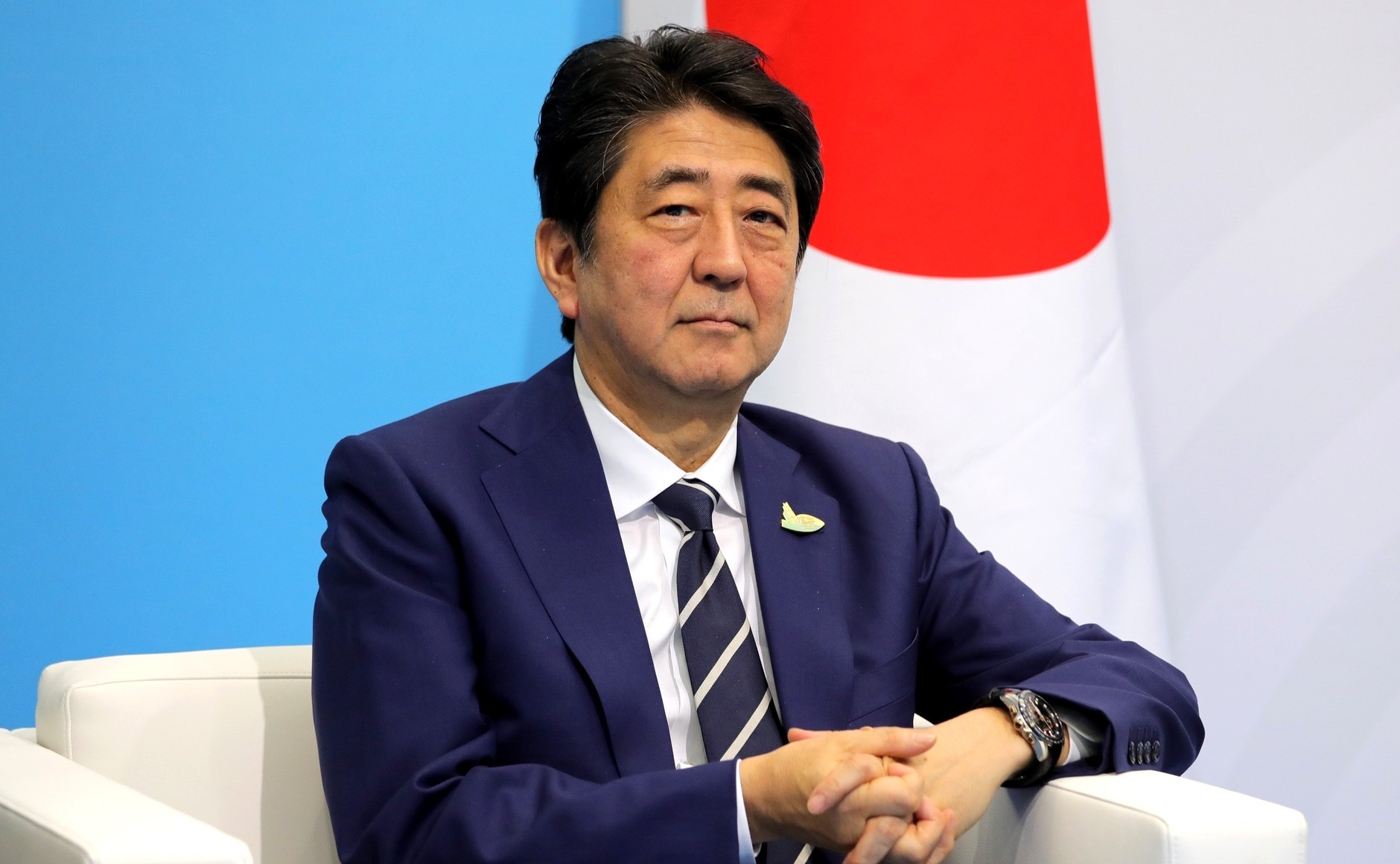 Japanese Prime Minister Shinzo Abe in front of the Japanese flag, earlier in 2017. Abe and the Japanese government are leading a push to provide universal health care to developing countries.