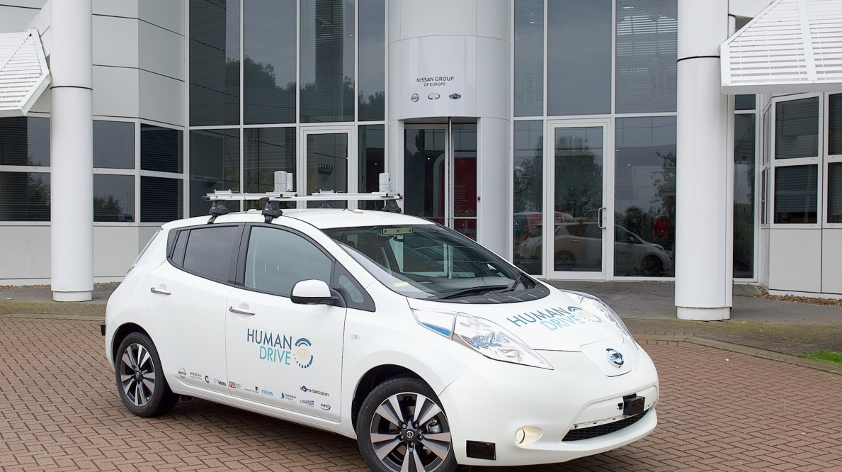 The HumanDrive Initiative's autonomous car, a while vehicle with a roof rack and a similar design to a Prius. This vehicle is slotted for a 200-mile self-driven test drive in 2019.