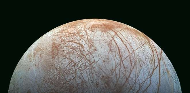 The surface of Europa, with bluish-white ice crisscrossed by reddish-brown streaks and cracks. Life on Europa may survive far beneath that icy shell by living off nuclear energy.