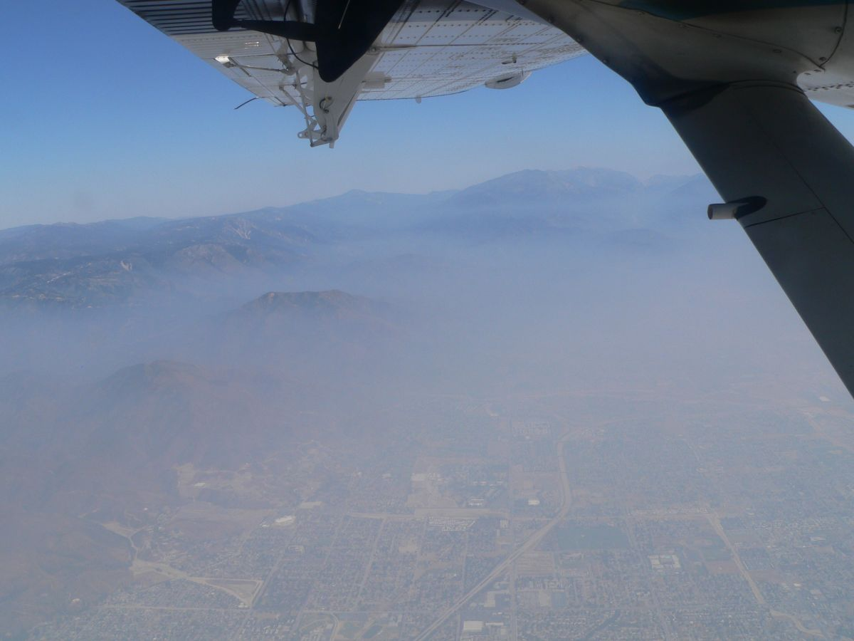 Air pollution in the form of smog over the city and hills of Los Angeles, as seen from within an airplane.