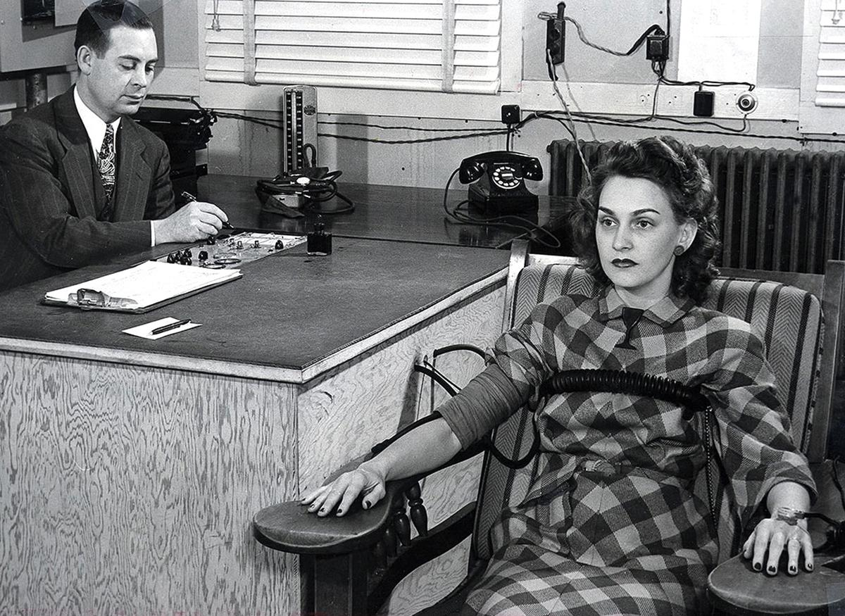 A black-and-white photo of a polygraph test being administered by an older man to a young woman in a checkered dress in an office, circa 1945.