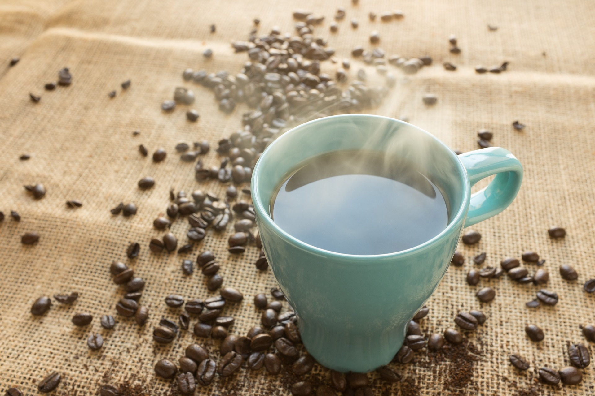 A cup of coffee in a blue cup on a sheet of burlap scattered with coffee beans. The science over whether this cup or those beans increase your cancer risk is still shaky.