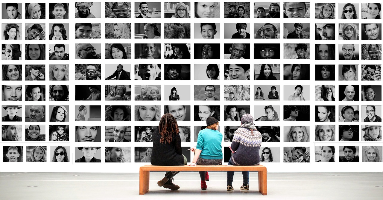 Three women sitting on a bench and looking at a wall covered in black and white images of various people. A mind-reading AI might be able to describe what each woman was seeing.