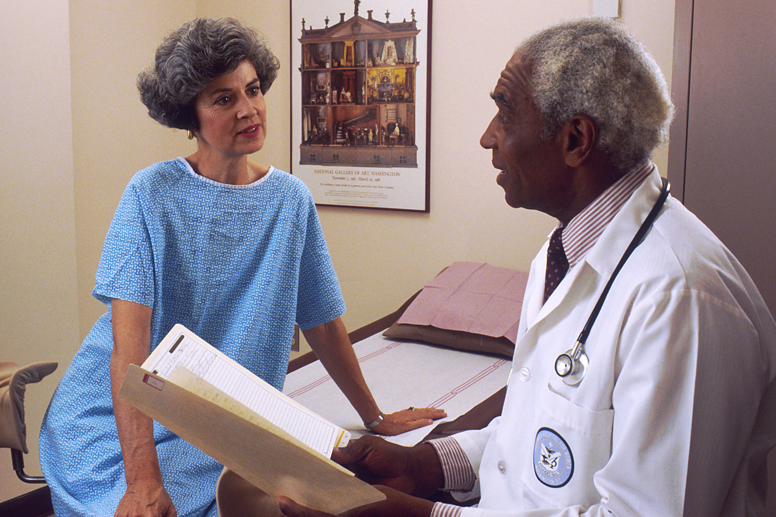 A black older male doctor consults with a white female patient in a hospital room, which should be standard in clinical trials.