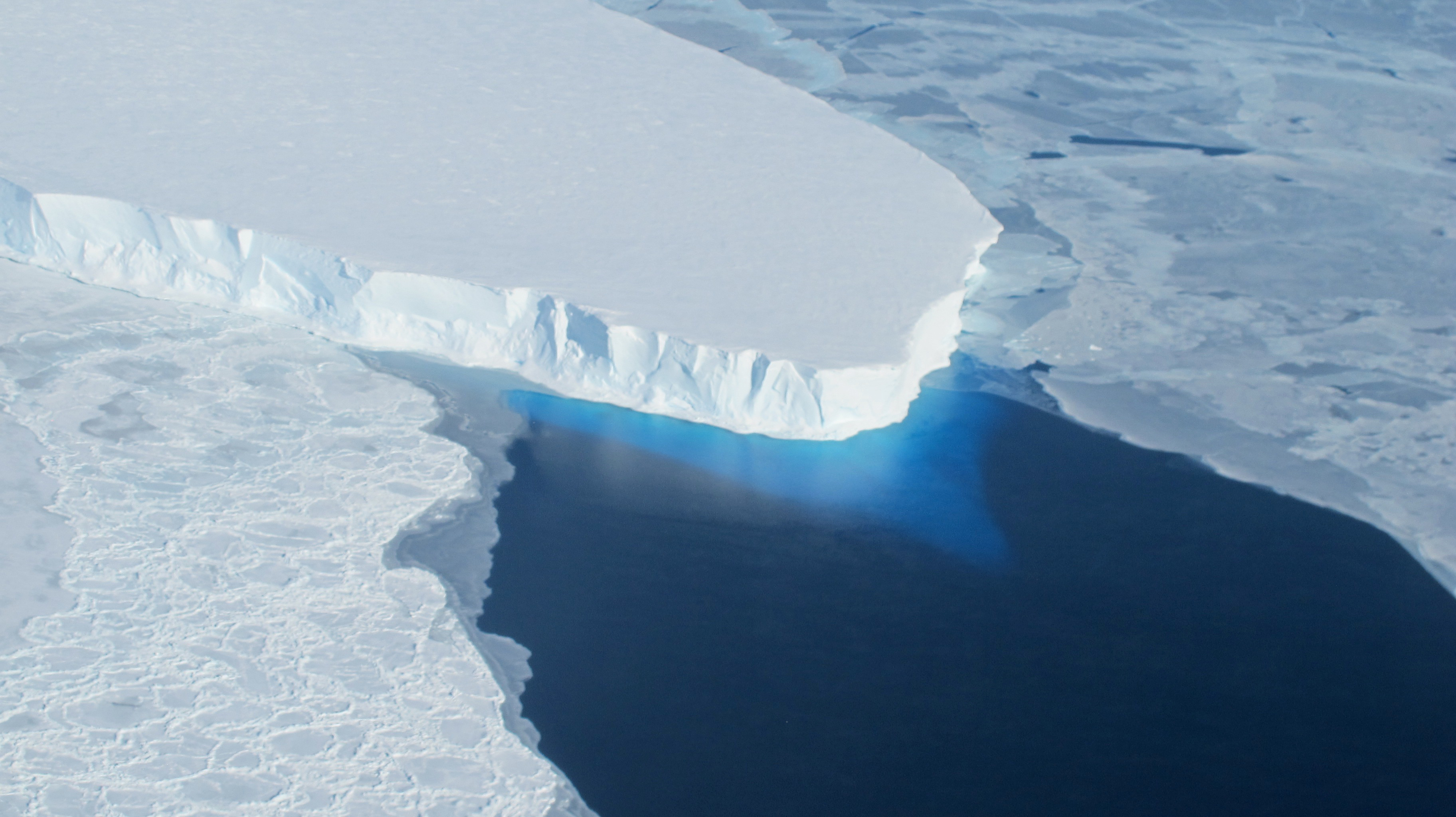 The Thwaites Glacier, shown here as a massive tongue of ice jutting out over blue water.