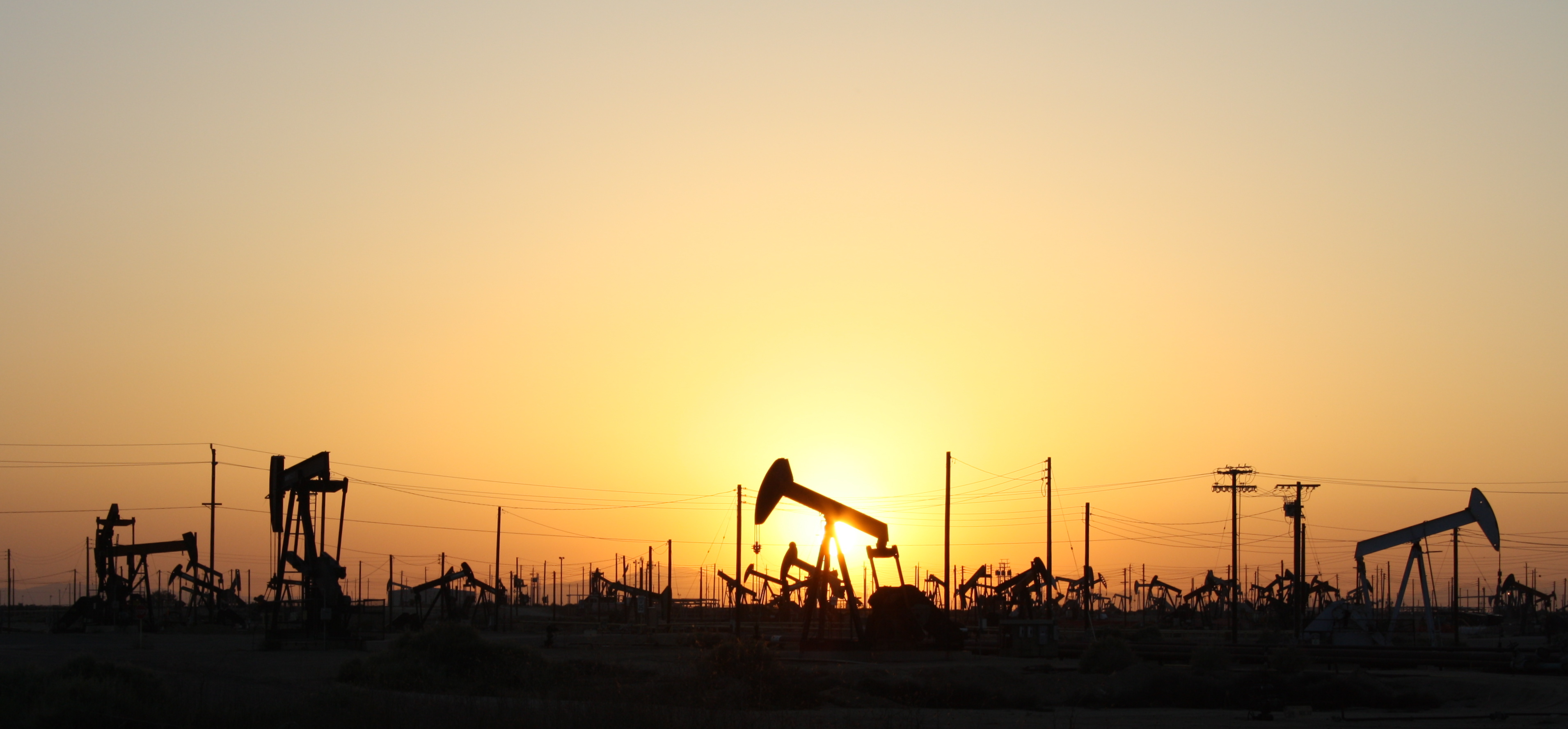 A field of pumpjacks in an oil field, a common source of methane, backlit by a sunset.