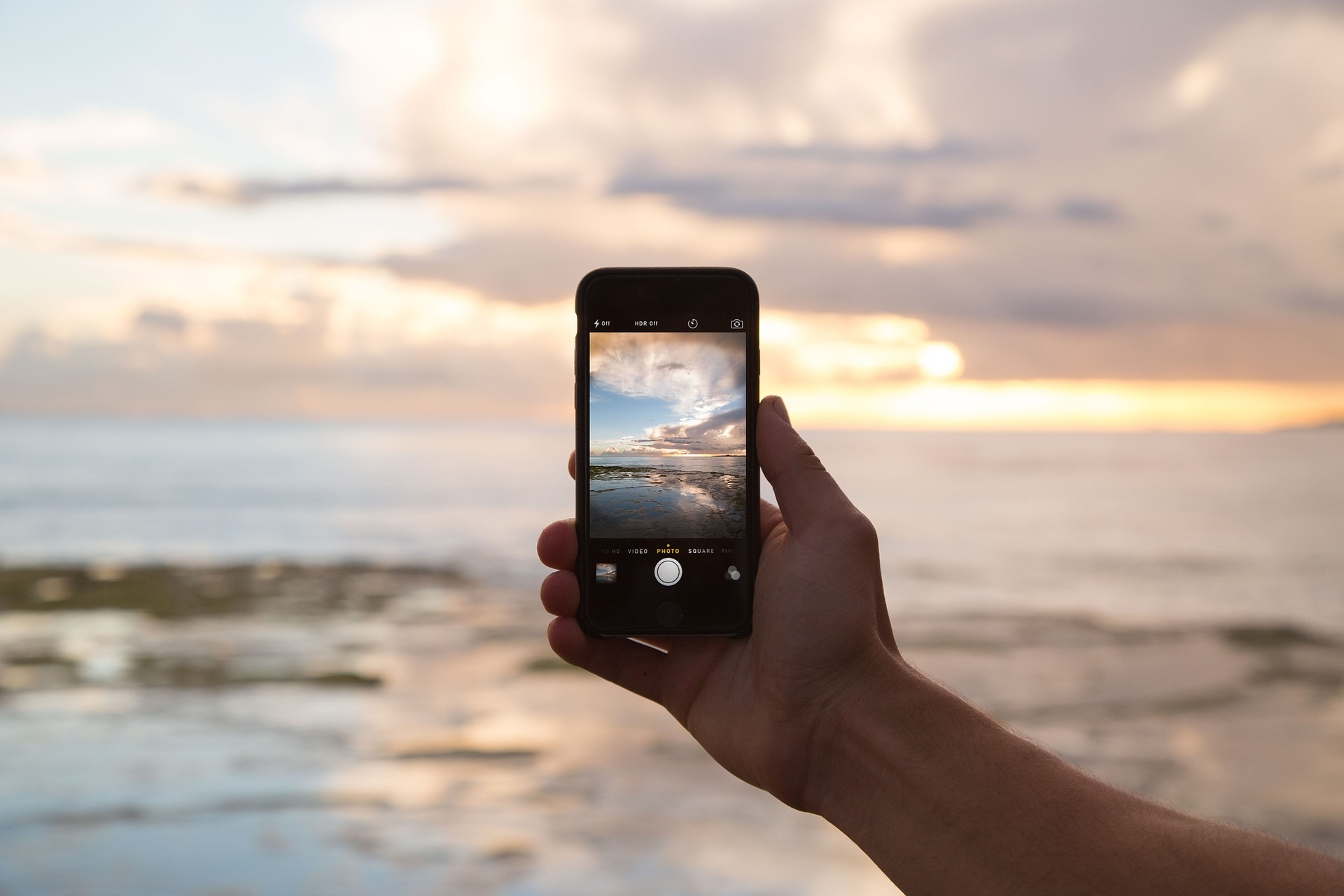 A hand holding a mobile phone taking a photo of a sunset over the ocean. Apps like Instagram encourage obsession with sharing content like this to the point that it may damage mental health.