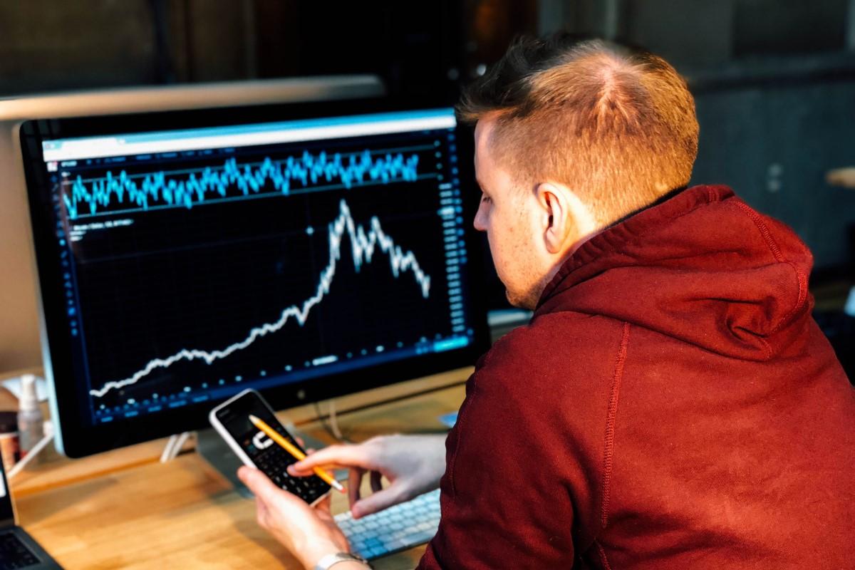 Man at computer investing.