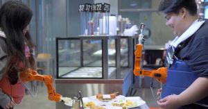 Arm-A-Dine is a robot arm that picks up food and feeds it to whichever human looks happiest. If you want dinner, you'll have to smile for the camera.