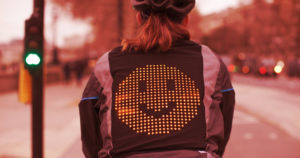 Ford has created a jacket for bicyclists that allows them to communicate with drivers using emoji displayed in LEDs on the rider's back.